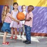 Παιδιά που παίζουν την καλαθοσφαίριση Στοκ Εικόνες