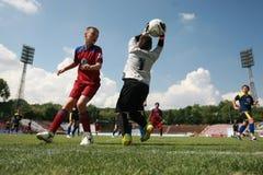 Παιδιά που παίζουν τον αγώνα ποδοσφαίρου ποδοσφαίρου Στοκ Φωτογραφία