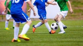 Παιδιά που παίζουν το παιχνίδι ποδοσφαίρου ποδοσφαίρου στον αθλητικό τομέα Τα αγόρια παίζουν τον αγώνα ποδοσφαίρου Στοκ Εικόνες