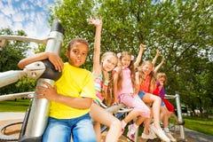 Παιδιά που παραμερίζουν τα χέρια που κάθονται στο στρογγυλό φραγμό Στοκ Εικόνες