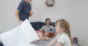 Παιδιά που παλεύουν με την πάλη στο κρεβάτι γονέων, ευτυχής οικογενειακή διασκέδαση το πρωί στο σπίτι απόθεμα βίντεο