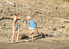 Παιδιά που περπατούν στη λάσπη στοκ εικόνες
