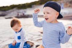 Παιδιά που πετούν τις πέτρες στον ωκεανό και τη χαρά αυτό Στοκ εικόνα με δικαίωμα ελεύθερης χρήσης