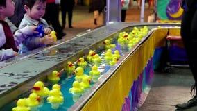 Παιδιά που πιάνουν το κίτρινο επιπλέον σώμα παπιών στο νερό απόθεμα βίντεο