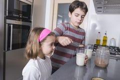 Παιδιά που προετοιμάζουν ένα ποτήρι του γάλακτος Στοκ Φωτογραφία