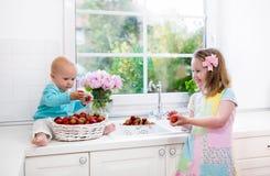 Παιδιά που πλένουν τη φράουλα στην άσπρη κουζίνα Στοκ φωτογραφία με δικαίωμα ελεύθερης χρήσης