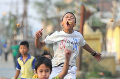Παιδιά που συμμετέχουν «στο δάγκωμα τα κρεμώντας μπισκότα» Στοκ Φωτογραφία