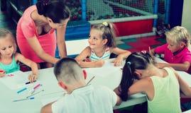 Παιδιά που σύρουν μαζί με το δάσκαλο στην ομάδα χόμπι Στοκ φωτογραφία με δικαίωμα ελεύθερης χρήσης