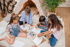 Παιδιά που σύρουν τις εικόνες με τα μολύβια στο σπίτι Στοκ εικόνα με δικαίωμα ελεύθερης χρήσης