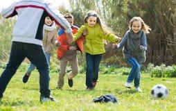 Παιδιά που τρέχουν μετά από τη σφαίρα στοκ φωτογραφίες