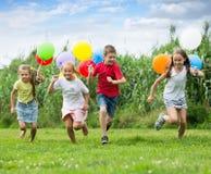 Παιδιά που τρέχουν με τα μπαλόνια αέρα στο πάρκο Στοκ εικόνες με δικαίωμα ελεύθερης χρήσης