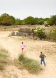 Παιδιά που τρέχουν σε ένα τοπίο αμμόλοφων στοκ εικόνες