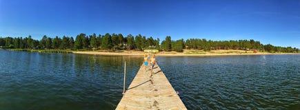 Παιδιά που τρέχουν σε μια αποβάθρα στη θερινή στρατοπέδευση λιμνών στοκ φωτογραφία με δικαίωμα ελεύθερης χρήσης