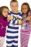 Παιδιά που φορούν τις χειμερινές πυτζάμες με το πάγωμα της κρύας έκφρασης στοκ εικόνα με δικαίωμα ελεύθερης χρήσης