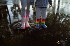Παιδιά που φορούν wellingtons στη λακκούβα Στοκ εικόνες με δικαίωμα ελεύθερης χρήσης