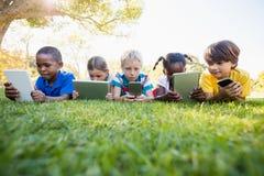 Παιδιά που χρησιμοποιούν την τεχνολογία κατά τη διάρκεια μιας ηλιόλουστης ημέρας Στοκ Εικόνες