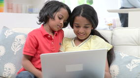 Παιδιά που χρησιμοποιούν το lap-top ενώ συνεδρίαση στον καναπέ στο σπίτι απόθεμα βίντεο