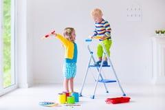 Παιδιά που χρωματίζουν τους τοίχους στο σπίτι Στοκ Φωτογραφία