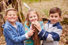 Παιδιά που χτίζουν το στρατόπεδο στο δάσος από κοινού στοκ εικόνες