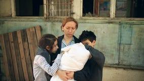 Παιδιά προσφύγων και η μητέρα τους με ένα παιδί στα όπλα τους ανάμεσα στα σπίτια Πόλεμος, σεισμός, πυρκαγιά, βομβαρδισμός απόθεμα βίντεο