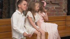 Παιδιά σε όμορφο ενός αναδρομικού στα ενδύματα σε έναν πάγκο μπροστά από τη κάμερα απόθεμα βίντεο