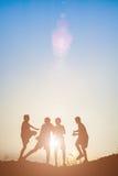 Παιδιά σκιαγραφιών που παίζουν στον ευτυχή χρόνο θερινού ηλιοβασιλέματος Στοκ Φωτογραφίες