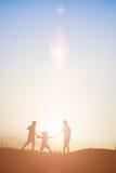 Παιδιά σκιαγραφιών που παίζουν στον ευτυχή χρόνο θερινού ηλιοβασιλέματος Στοκ φωτογραφίες με δικαίωμα ελεύθερης χρήσης