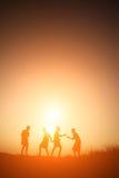 Παιδιά σκιαγραφιών που παίζουν στον ευτυχή χρόνο θερινού ηλιοβασιλέματος Στοκ φωτογραφία με δικαίωμα ελεύθερης χρήσης