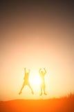 Παιδιά σκιαγραφιών που παίζουν στον ευτυχή χρόνο θερινού ηλιοβασιλέματος Στοκ Εικόνες