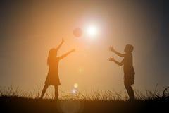 Παιδιά σκιαγραφιών που παίζουν το ποδόσφαιρο στο ηλιοβασίλεμα ουρανού Χρόνος επάνω Στοκ φωτογραφίες με δικαίωμα ελεύθερης χρήσης