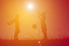 Παιδιά σκιαγραφιών που παίζουν το ποδόσφαιρο στο ηλιοβασίλεμα ουρανού Χρόνος επάνω Στοκ Φωτογραφία