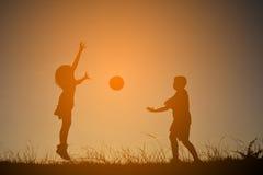 Παιδιά σκιαγραφιών που παίζουν το ποδόσφαιρο στο ηλιοβασίλεμα ουρανού Χρόνος επάνω Στοκ Εικόνα