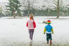 Παιδιά στα ζωηρόχρωμα ενδύματα που περπατούν σε ένα πάρκο κάτω από τις χιονοπτώσεις Στοκ φωτογραφία με δικαίωμα ελεύθερης χρήσης