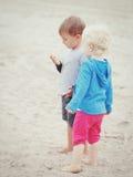 Παιδιά στα θαλασσινά κοχύλια επιλογής παιχνιδιού παραλιών στοκ εικόνα