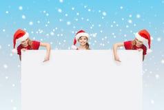 Παιδιά στα καπέλα αρωγών santa με τον κενό πίνακα Στοκ εικόνες με δικαίωμα ελεύθερης χρήσης