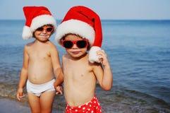 Παιδιά στα καπέλα Χριστουγέννων ενάντια στη θάλασσα Στοκ φωτογραφία με δικαίωμα ελεύθερης χρήσης
