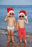 Παιδιά στα καπέλα Χριστουγέννων ενάντια στη θάλασσα Στοκ εικόνα με δικαίωμα ελεύθερης χρήσης