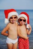 Παιδιά στα καπέλα Χριστουγέννων ενάντια στη θάλασσα Στοκ Εικόνες