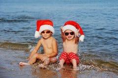 Παιδιά στα καπέλα Χριστουγέννων ενάντια στη θάλασσα στοκ εικόνα