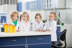 Παιδιά στο εργαστήριο επιστήμης που φορά τα παλτά και που στέκεται στον πίνακα στοκ φωτογραφία με δικαίωμα ελεύθερης χρήσης