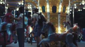 Παιδιά στο ιπποδρόμιο εύθυμος-πηγαίνω-γύρω από το γύρο διασκέδασης με τα καλπάζοντας άλογα απόθεμα βίντεο