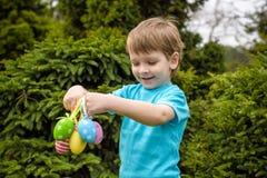 Παιδιά στο κυνήγι αυγών Πάσχας στον ανθίζοντας κήπο άνοιξη Παιδιά που ψάχνουν για τα ζωηρόχρωμα αυγά στο λιβάδι λουλουδιών Αγόρι  Στοκ φωτογραφία με δικαίωμα ελεύθερης χρήσης