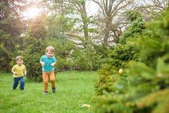 Παιδιά στο κυνήγι αυγών Πάσχας στον ανθίζοντας κήπο άνοιξη Παιδιά που ψάχνουν για τα ζωηρόχρωμα αυγά στο λιβάδι λουλουδιών Αγόρι  Στοκ Φωτογραφία