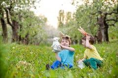 Παιδιά στο κυνήγι αυγών Πάσχας στον ανθίζοντας κήπο άνοιξη Παιδιά που ψάχνουν για τα ζωηρόχρωμα αυγά στο λιβάδι λουλουδιών Αγόρι  Στοκ Εικόνες