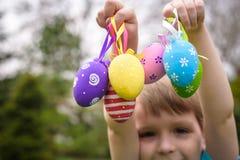 Παιδιά στο κυνήγι αυγών Πάσχας στον ανθίζοντας κήπο άνοιξη Παιδιά που ψάχνουν για τα ζωηρόχρωμα αυγά στο λιβάδι λουλουδιών Αγόρι  Στοκ φωτογραφίες με δικαίωμα ελεύθερης χρήσης