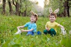 Παιδιά στο κυνήγι αυγών Πάσχας στον ανθίζοντας κήπο άνοιξη Παιδιά που ψάχνουν για τα ζωηρόχρωμα αυγά στο λιβάδι λουλουδιών Αγόρι  Στοκ Εικόνα