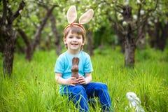 Παιδιά στο κυνήγι αυγών Πάσχας στον ανθίζοντας κήπο άνοιξη Παιδιά που ψάχνουν για τα ζωηρόχρωμα αυγά στο λιβάδι λουλουδιών Αγόρι  Στοκ Φωτογραφίες