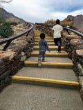 Παιδιά στο παιχνίδι, δύο νέα αγόρια που συσσωρεύουν τα σκαλοπάτια Στοκ Εικόνες