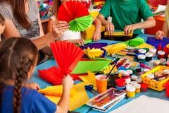 Παιδιά σχολείου με το ψαλίδι στα χέρια παιδιών που κόβουν το έγγραφο στοκ εικόνες