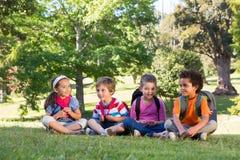 Παιδιά σχολείου που κάθονται στη χλόη Στοκ φωτογραφία με δικαίωμα ελεύθερης χρήσης